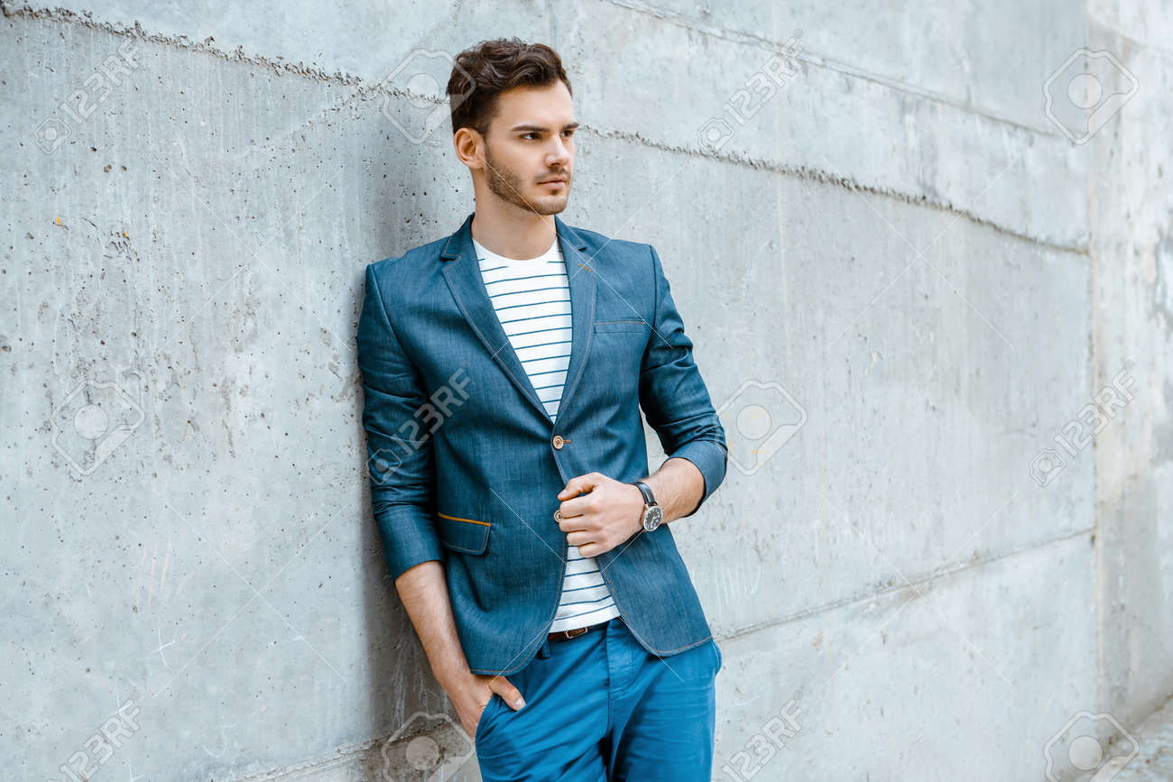 Portrait of stylish handsome young man with bristle standing outdoors and leaning on wall. Man wearing jacket and shirt Standard-Bild - 47874025