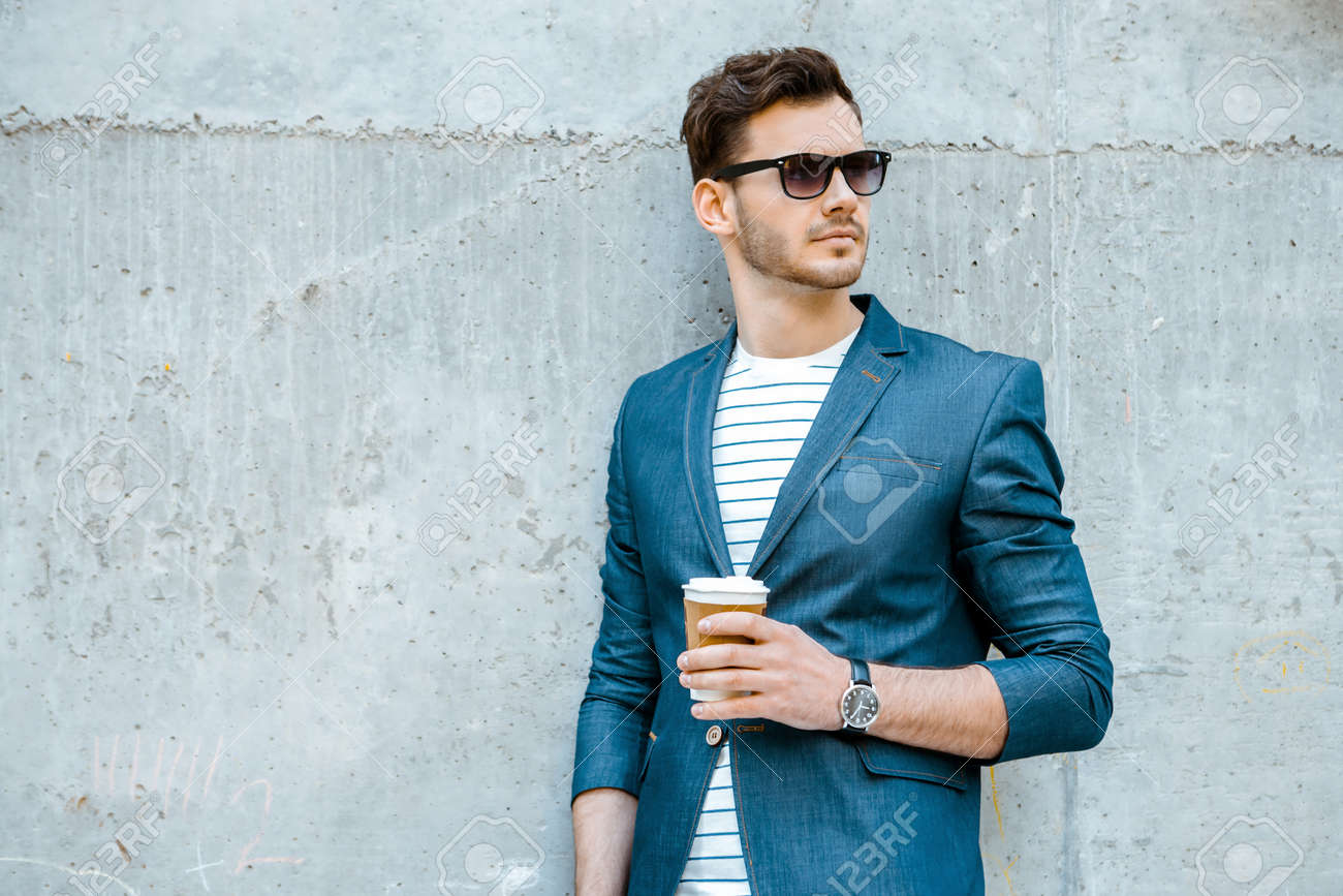 Portrait of stylish handsome young man with bristle standing outdoors and leaning on wall. Man wearing jacket, sunglasses, shirt and holding cup of coffee Standard-Bild - 47874026