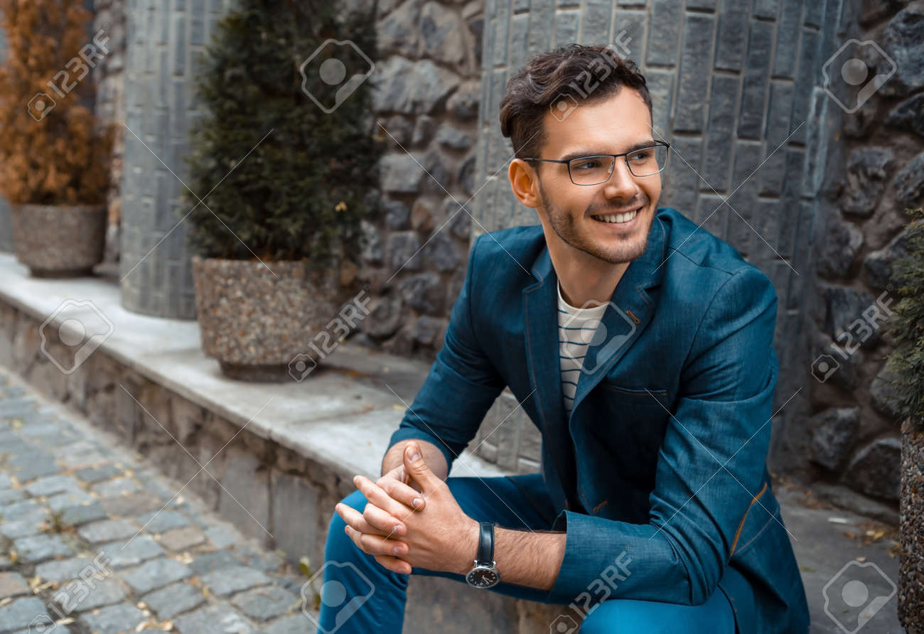 Portrait of stylish handsome young man with bristle sitting on parapet outdoors. Man wearing jacket and shirt Standard-Bild - 47874030