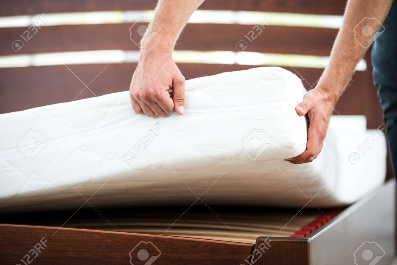 Close up photo of young man demonstrating quality of mattress Standard-Bild - 49654399