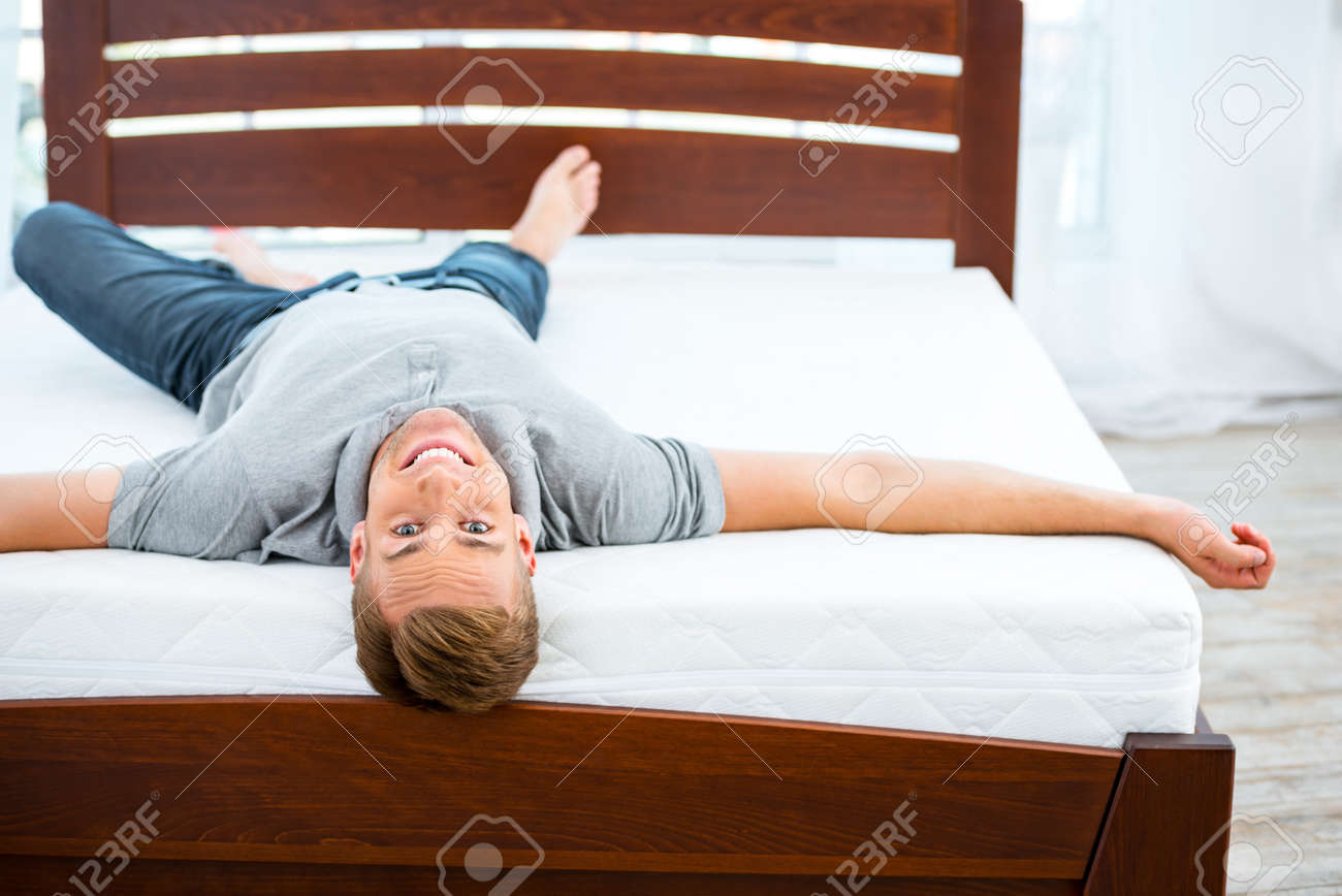Lit Pour Jeune Homme photo de jeune homme allongé sur un beau lit blanc. jeune homme démontrant  la qualité du matelas
