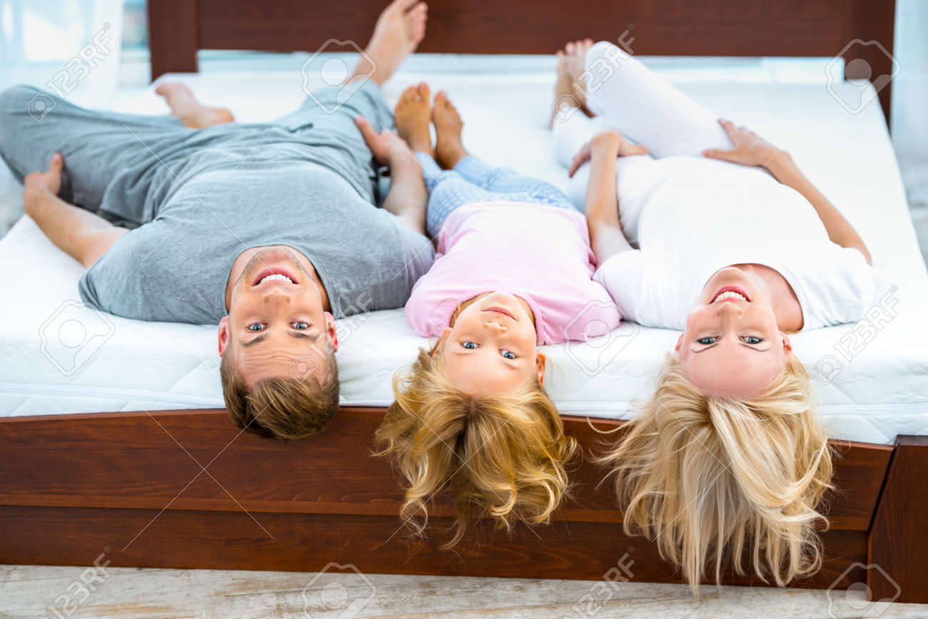 Photo of young family of three lying on nice white bed. Young family demonstrating quality of mattress Standard-Bild - 49654371