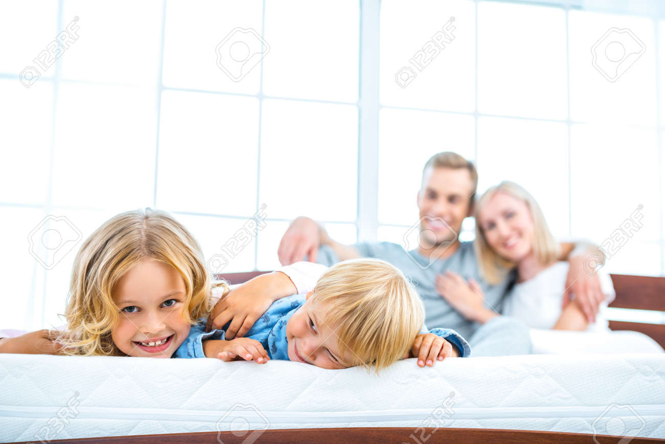 Photo of young family of four lying on nice white bed. Young family demonstrating quality of mattress Standard-Bild - 49654372