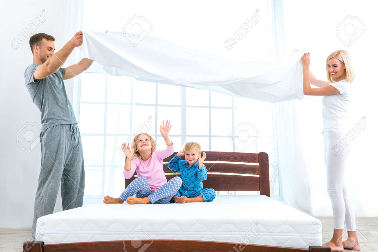 Photo of loving family of four making bed. Young family demonstrating quality of mattress and holding blanket Standard-Bild - 49654379