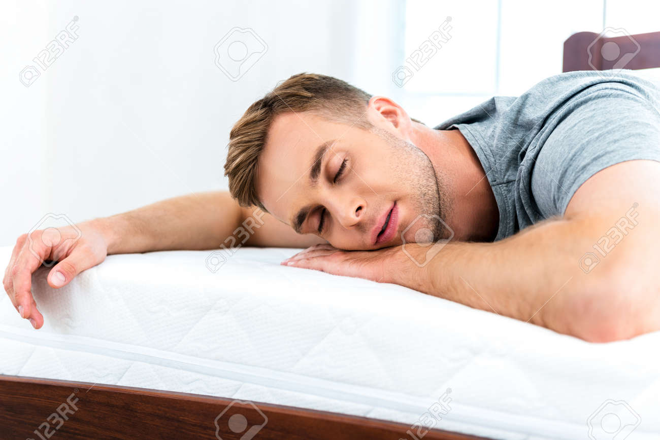 Photo of young man sleeping on nice white bed. Young man demonstrating quality of mattress Standard-Bild - 49654381