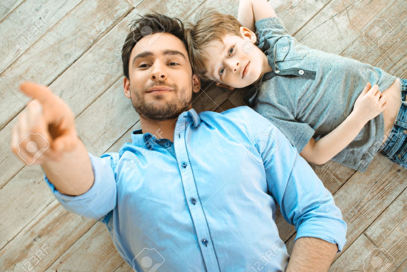 Nice family photo of little boy and his father. Boy and dad smiling and lying on wooden floor. Father pointing at camera Standard-Bild - 49654347
