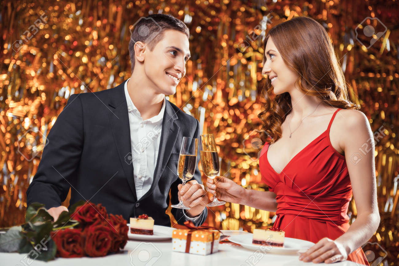 Romantic photo of beautiful couple on glitter gold background. Couple having date at Valentine's Day. Lovers having dinner. There are glasses with champagne, desserts, roses and gift on table Standard-Bild - 54663558