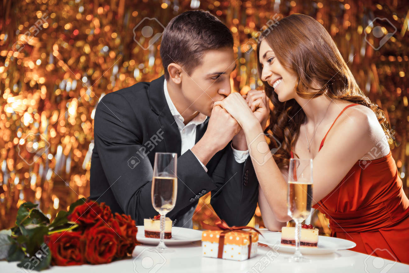 Romantic photo of beautiful couple on glitter gold background. Couple having date at Valentine's Day. Lovers having dinner. There are glasses with champagne, desserts, roses and gift on table Standard-Bild - 54663591