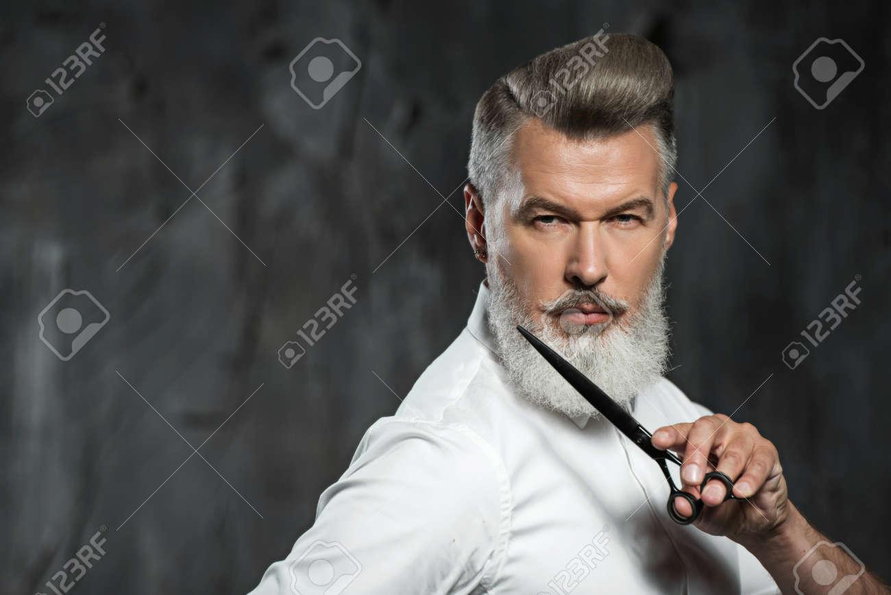 Portrait of stylish professional hairdresser with beard. Man wearing shirt, looking aside and holding scissors near his beard Standard-Bild - 54201117