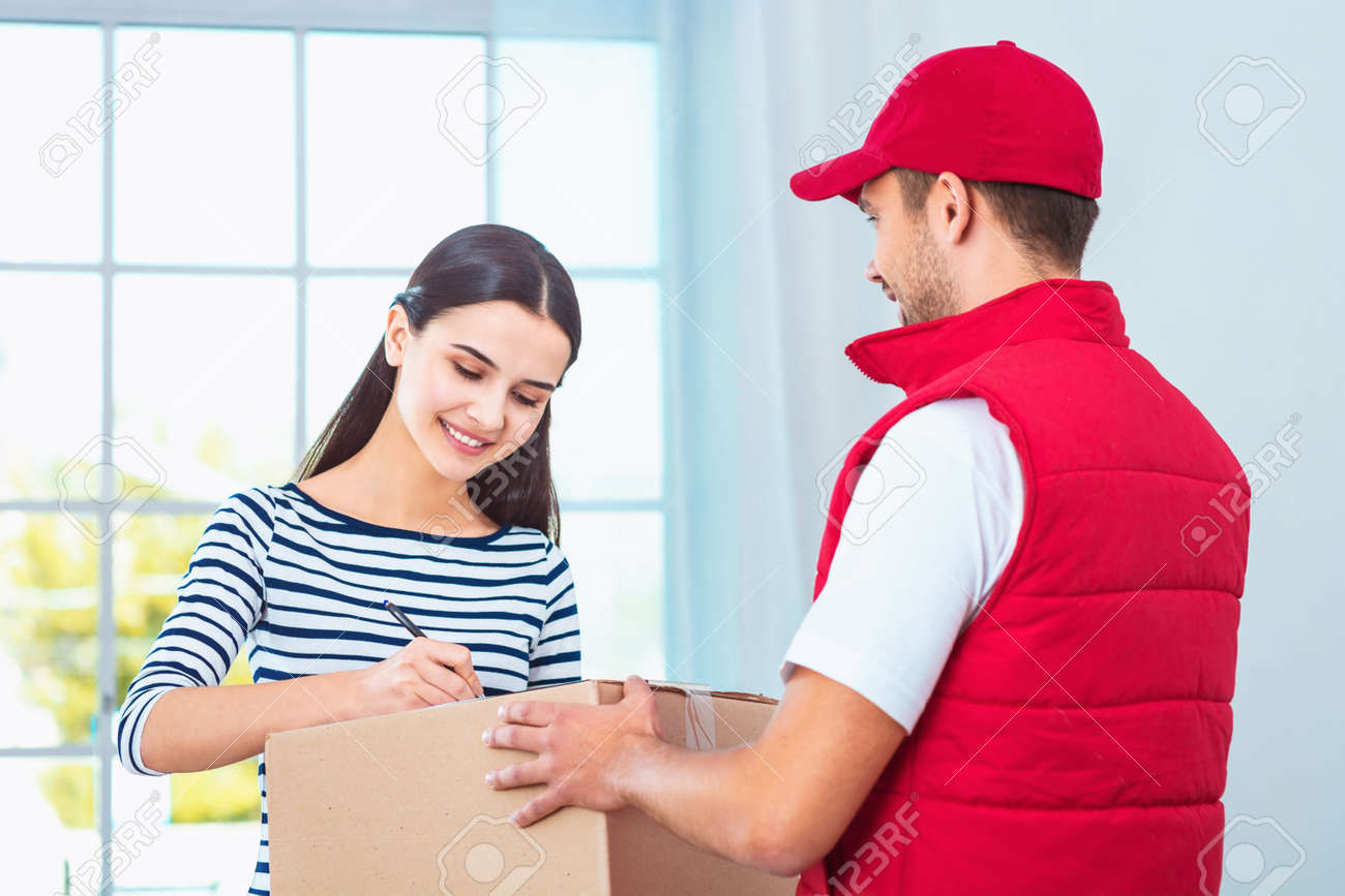 Delivery service worker in uniform delivering parcel to woman. Woman signing document on box Standard-Bild - 54205042
