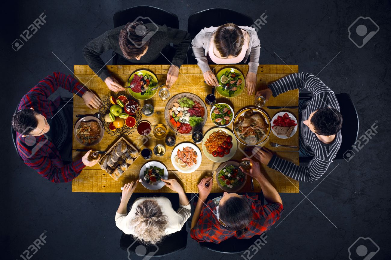 Top view creative photo of friends sitting at wooden vintage table. Friends of six having dinner. They with plates full of delicious meal and glasses with drinks - 54207294