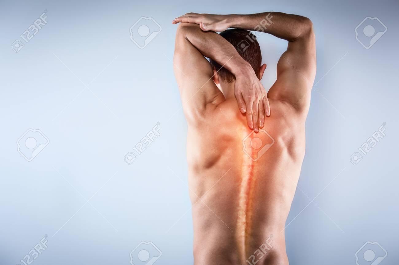 Prise de vue en studio de beau jeune homme au torse nu. Homme souffrant de  maux de cou. Tache rouge à l'arrière