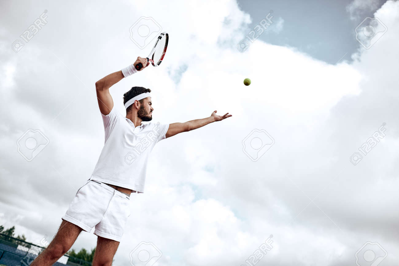 Professional tennis player playing a game of tennis on a court. He is about to hit the ball with the racket. The ball is suspended in the air. - 107827367