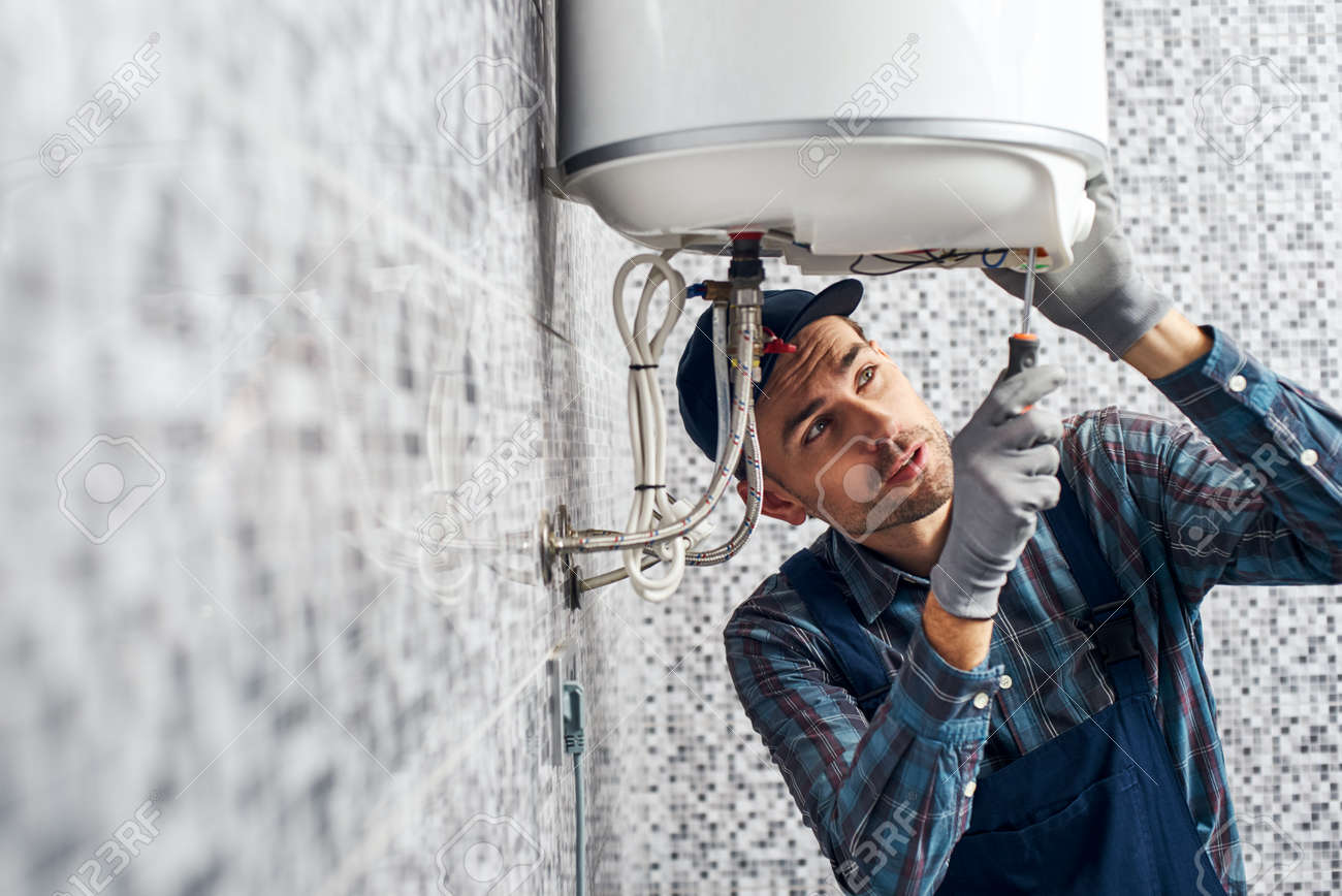 Almost done. Worker set up electric heating boiler at home bathroom - 117135905