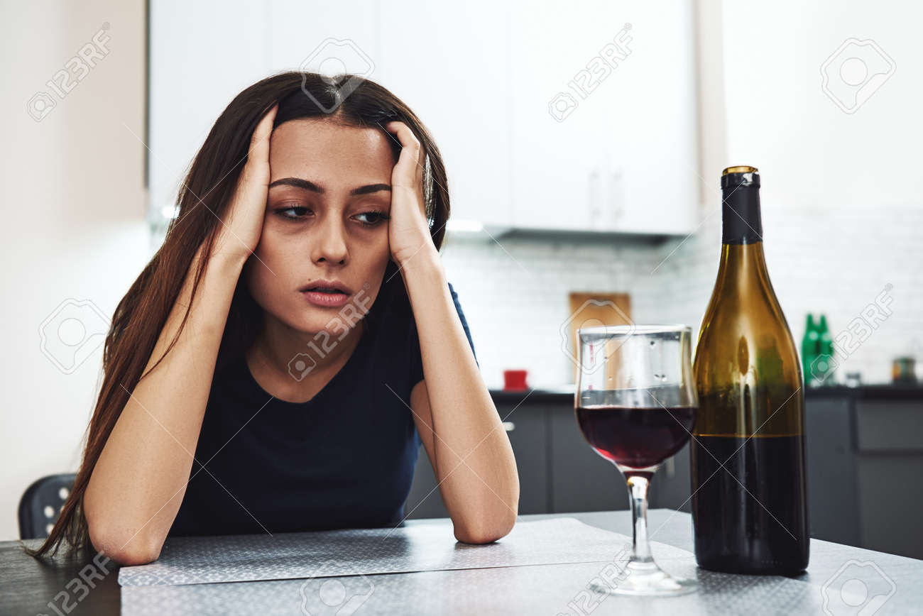 It's gonna get harder before it gets easier. But it will get better, you just gotta make it through the hard stuff first. Drunk girl looking at bottle of alcohol. Soccial issue alcoholism. - 118554413