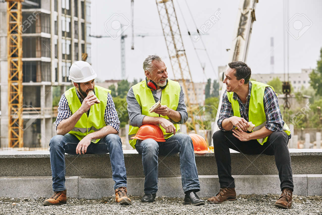 Time for a break. Group of builders in working uniform are eating sandwiches and talking while sitting on stone surface against construction site. Building concept. Lunch concept - 120919223