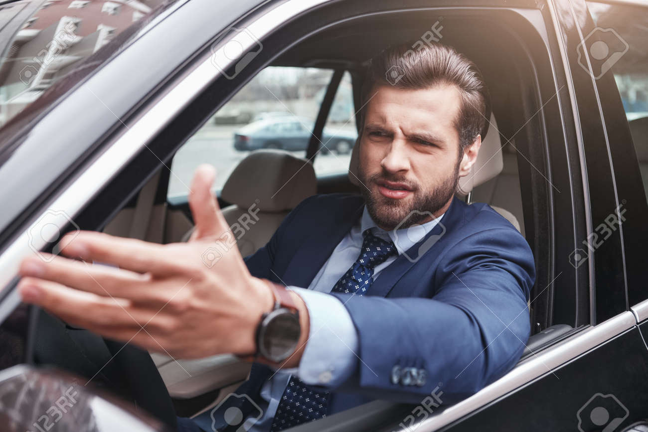 I dont like it. Angry and emotional businessman in formal wear is gesturing and making a grimace while driving his car. - 124837969