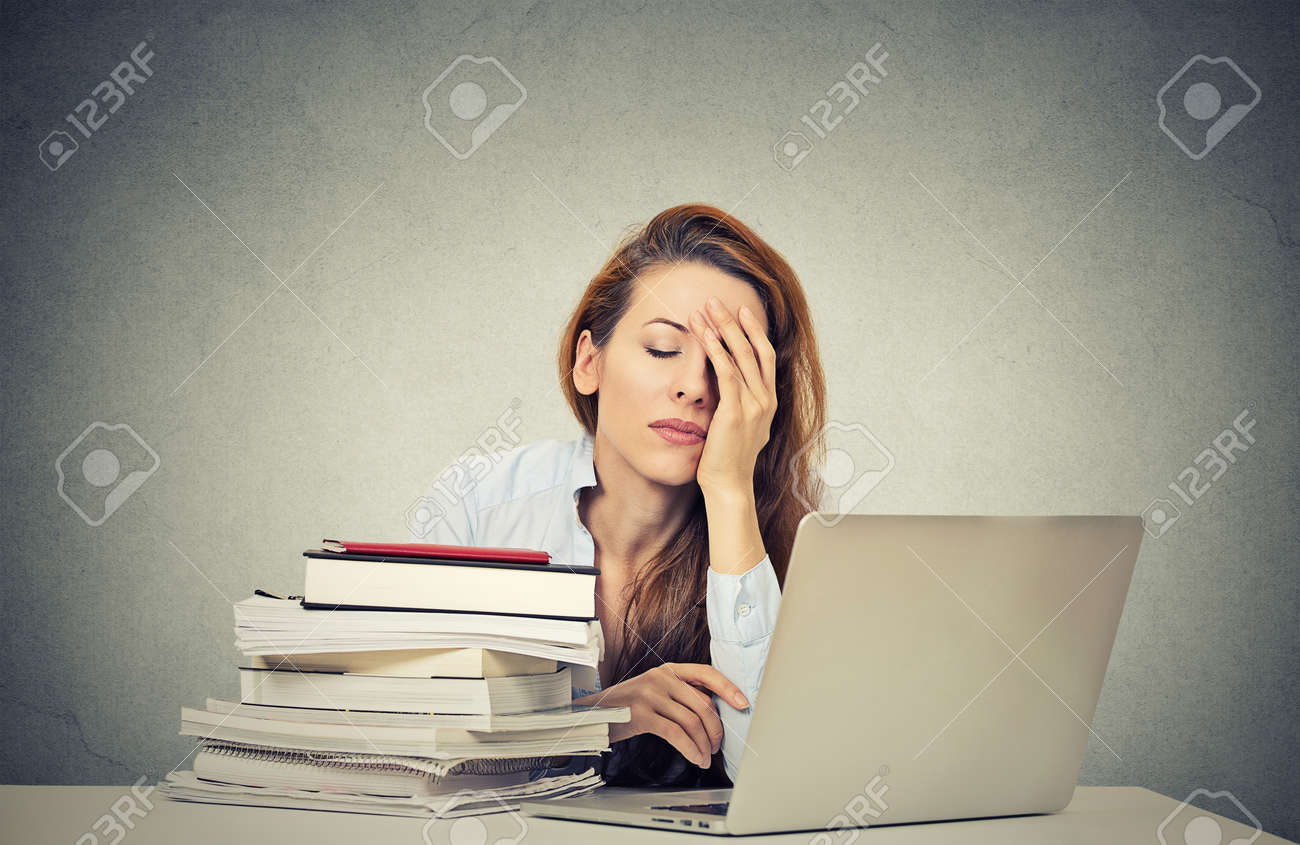 too much work tired sleepy young w sitting at her desk stock photo too much work tired sleepy young w sitting at her desk books in front of laptop computer isolated grey wall office background