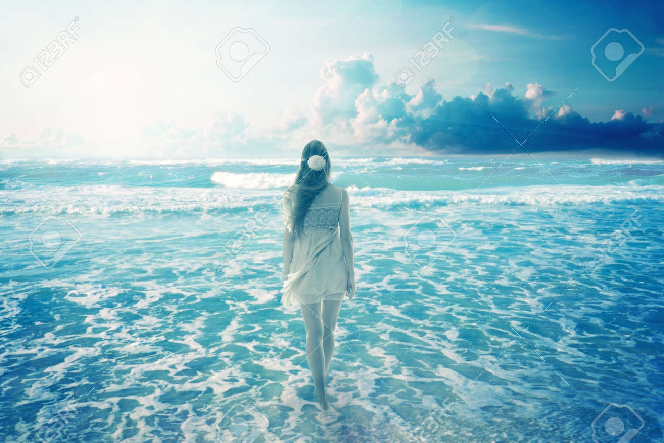 young woman walking on a dreamy beach enjoying ocean colorful