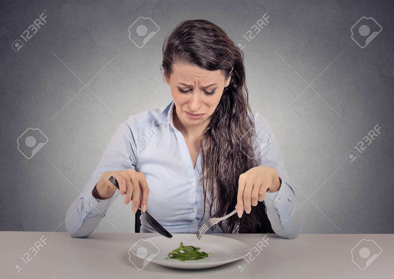 Young woman tired of diet restrictions eating green salad sitting at table isolated grey wall background. Human face expression emotion. Nutrition concept - 40353346