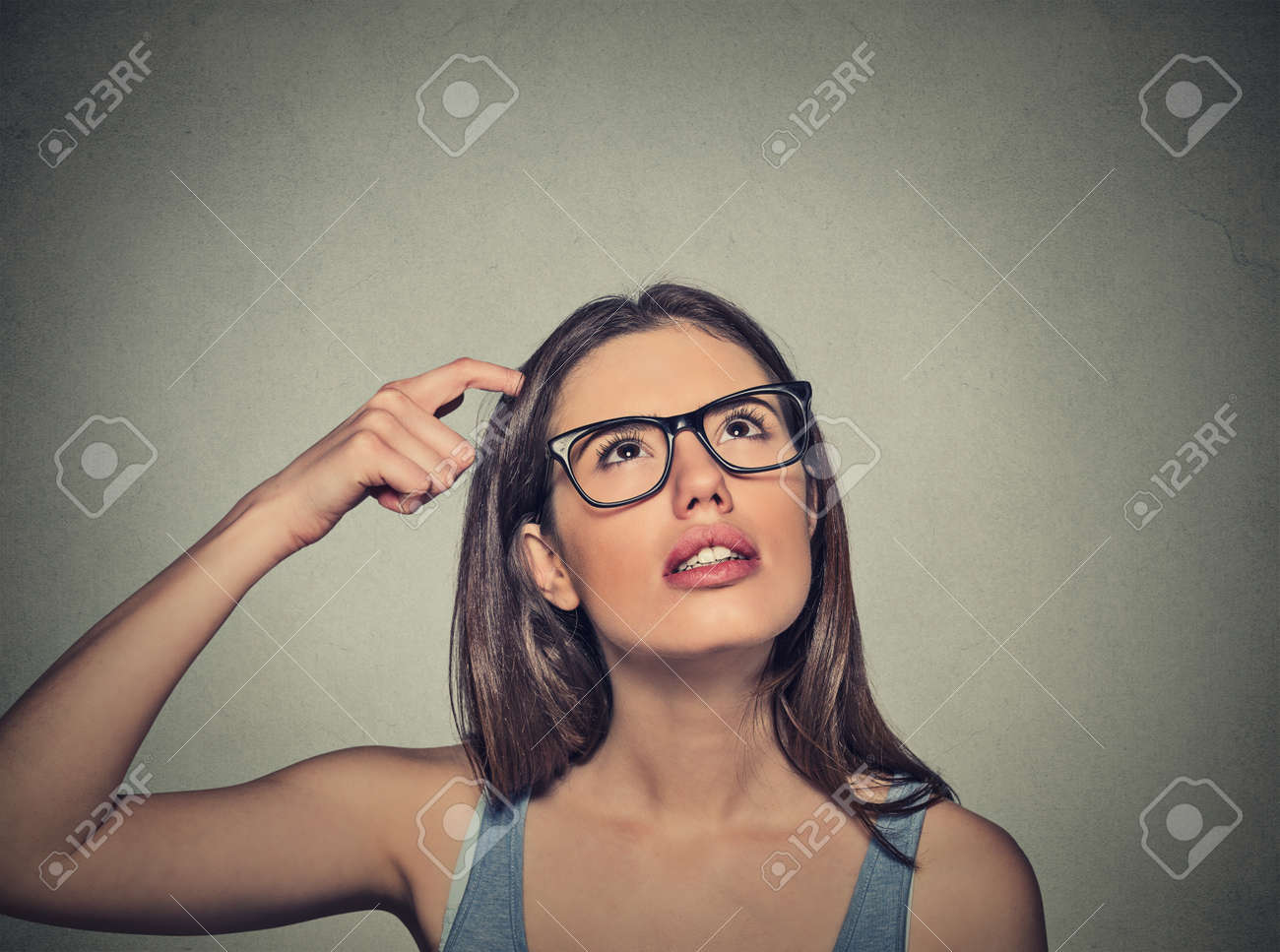Closeup portrait young woman scratching head, thinking daydreaming deeply about something looking up isolated on gray wall background. Human facial expressions, emotions, feelings, signs, symbols - 43388417