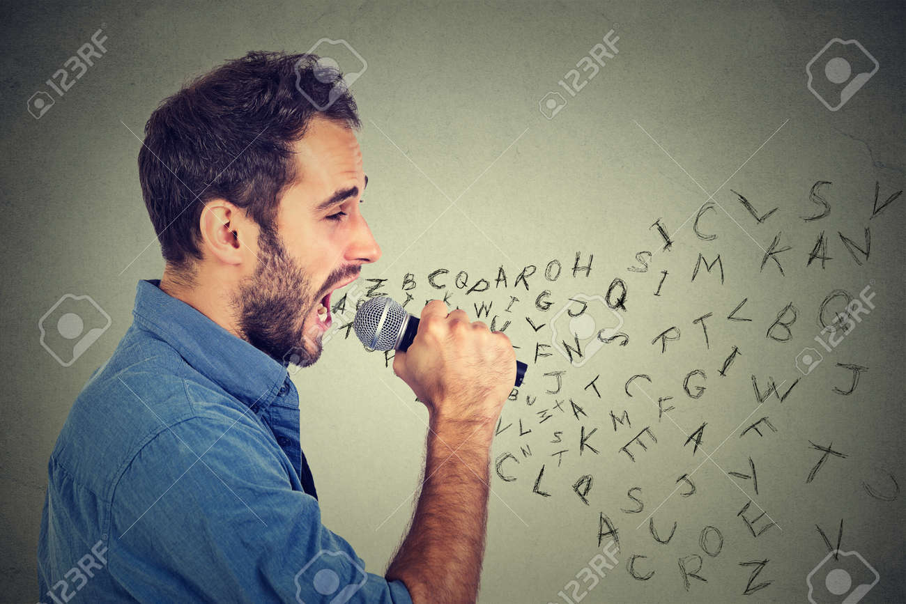 young man singing in microphone with alphabet letters coming stock