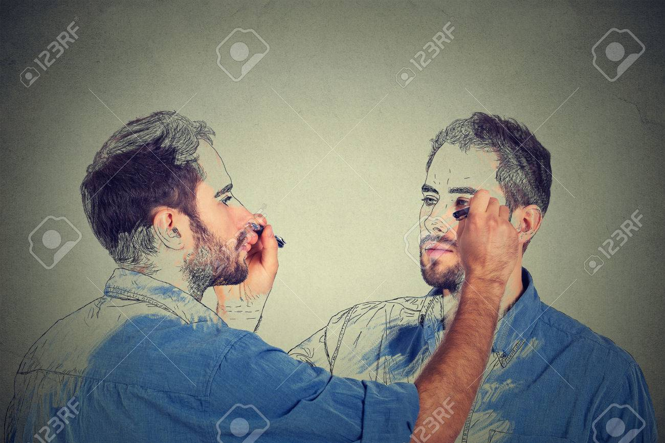 Create yourself concept. Good looking young man drawing a picture, sketch of himself on grey wall background. Human face expressions, creativity - 50100628