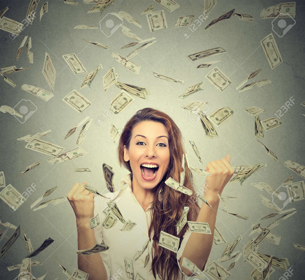 Portrait happy woman exults pumping fists ecstatic celebrates success under a money rain falling down dollar bills banknotes isolated on gray wall background with copy space - 50995260
