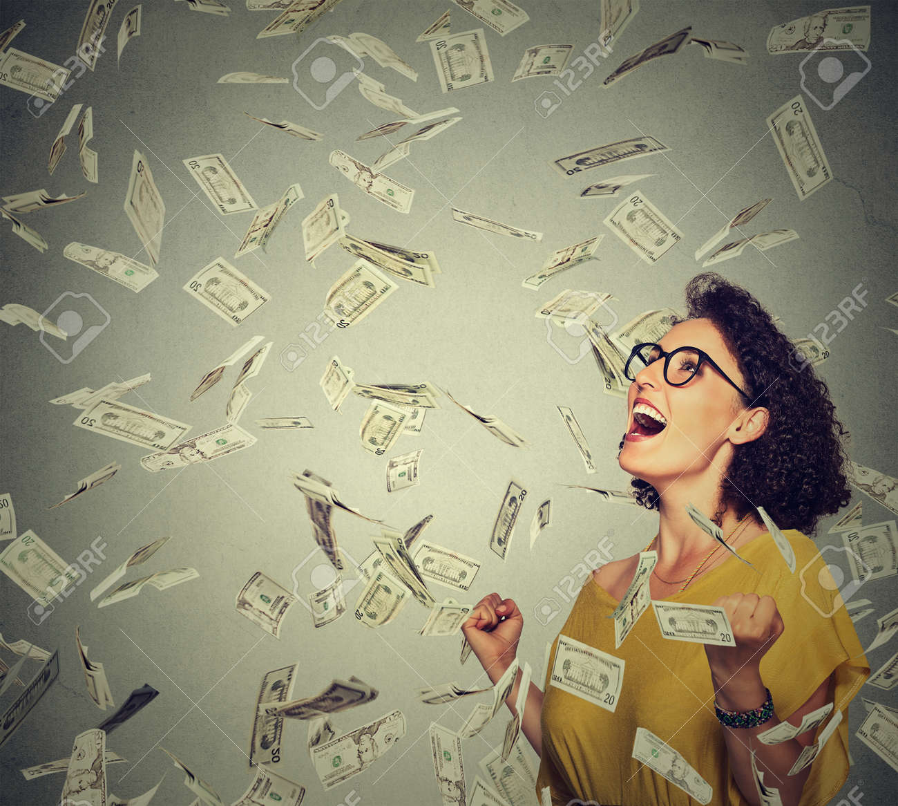 Portrait happy woman in glasses exults pumping fists ecstatic celebrates success under a money rain falling down dollar bills banknotes isolated on gray wall background with copy space - 50995261