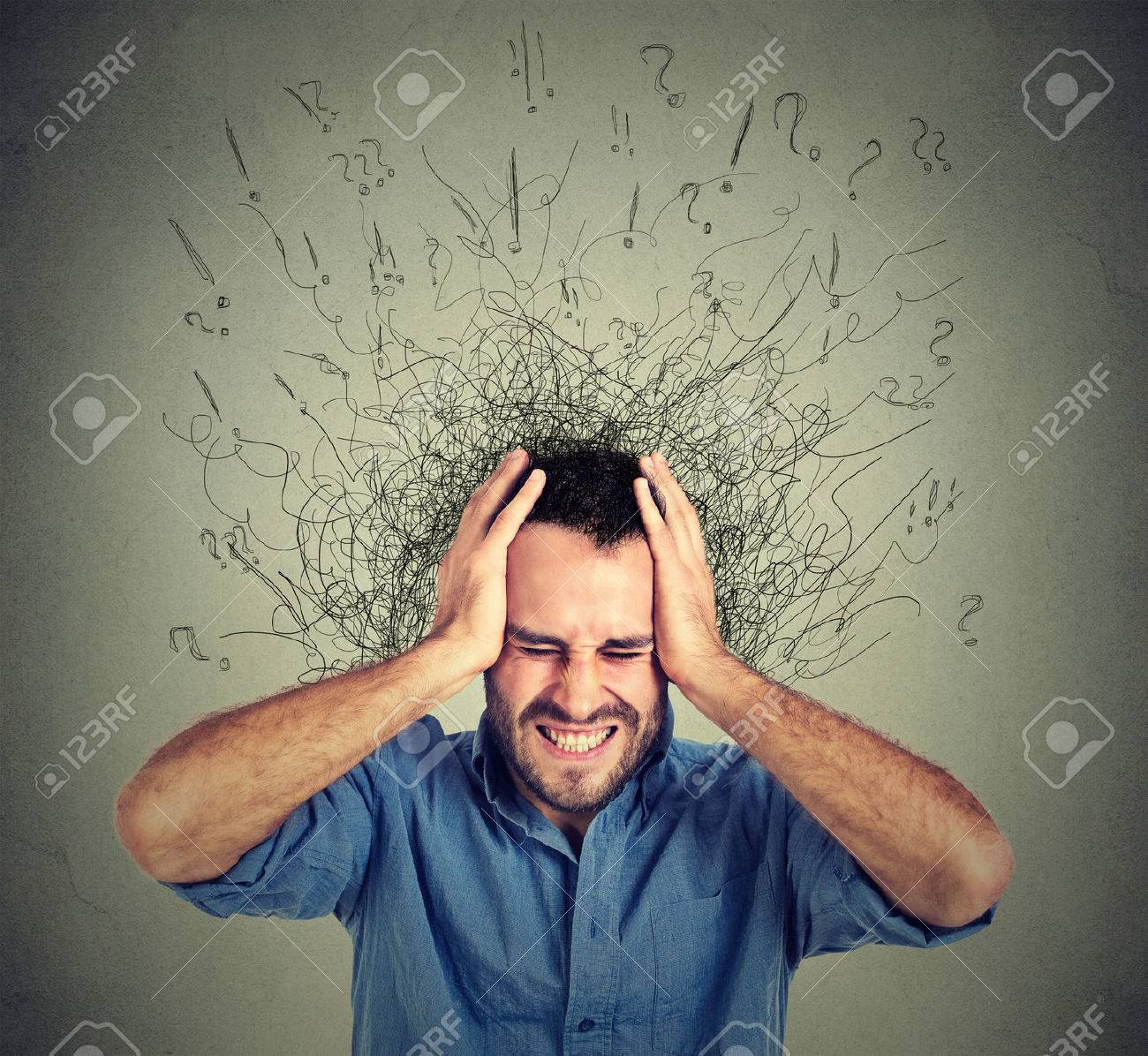 Stressed man upset frustrated has too many thoughts with brain melting into lines question marks. Obsessive compulsive, adhd, anxiety disorder. Negative human emotions face expression feelings - 51742552