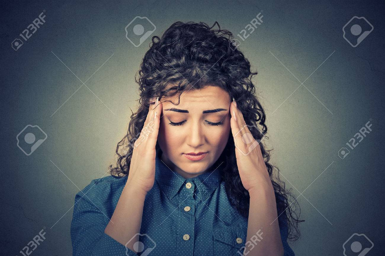Closeup sad young woman with worried stressed face expression having headache isolated on gray wall background. Human emotions, mental health concept - 52660416