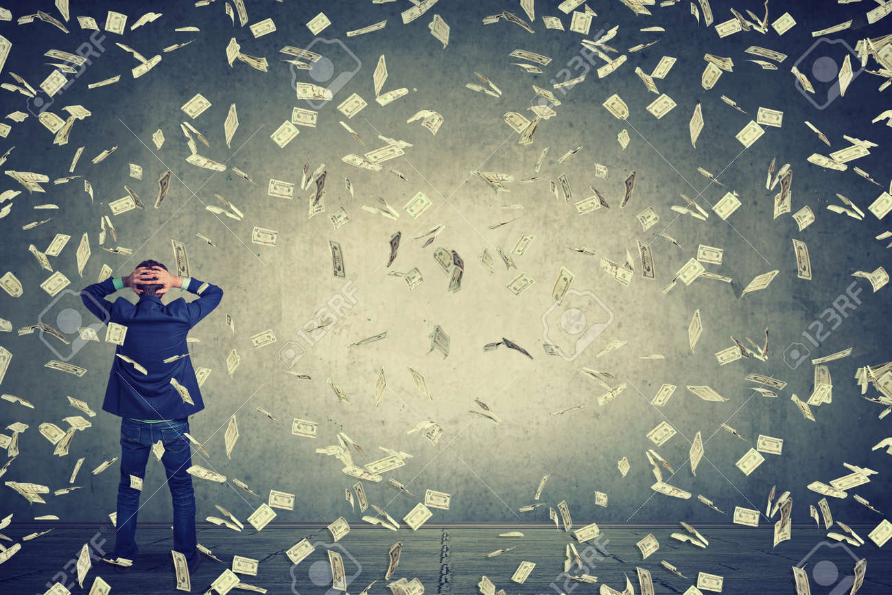 Rear back view of business man standing in front of a wall under money rain dollar banknotes falling down, hands on head wondering what to do next. Full body length of businessman facing the wall - 55040263