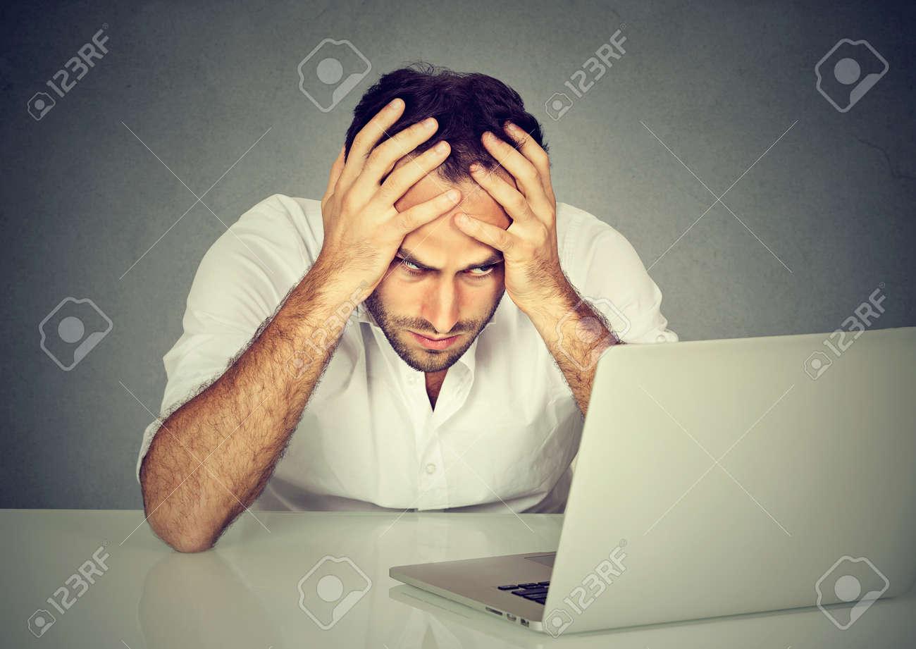 Trop de travail à faire. stressé jeune homme assis à son bureau
