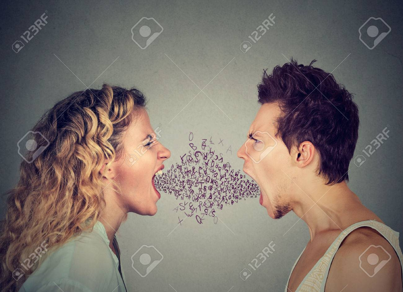 Side profile angry young couple man and woman screaming face to face with alphabet letters coming out of open mouth. Negative face expression emotion - 64449687