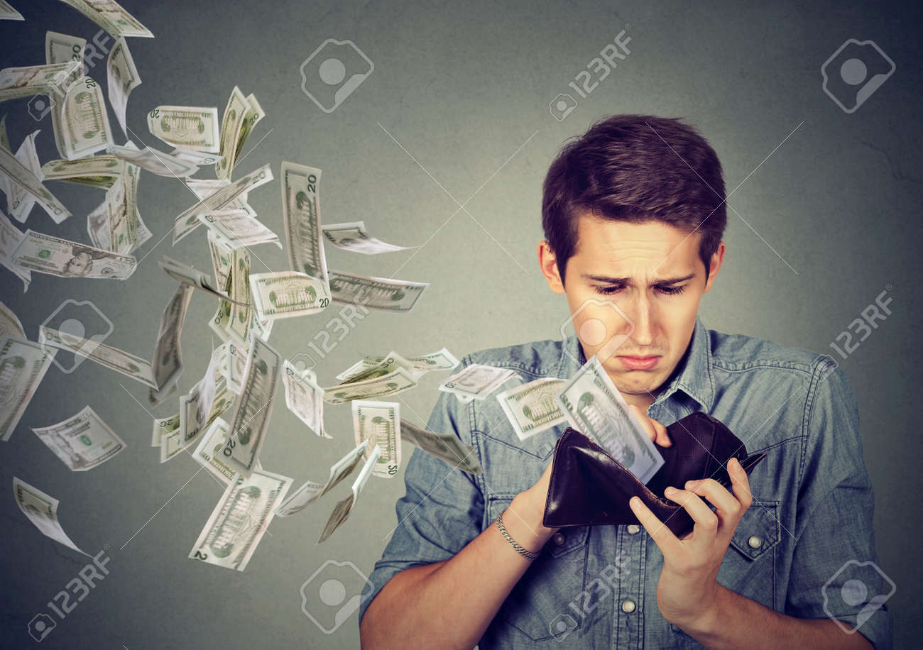 Sad man looking at his wallet with money dollar banknotes flying out away - 68416070