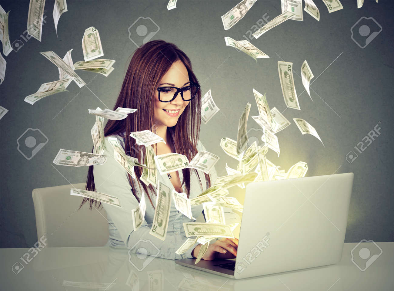 Professional smart young woman using a laptop building online business making money dollar bills cash coming out of computer. Beginner IT entrepreneur success economy concept - 74961839