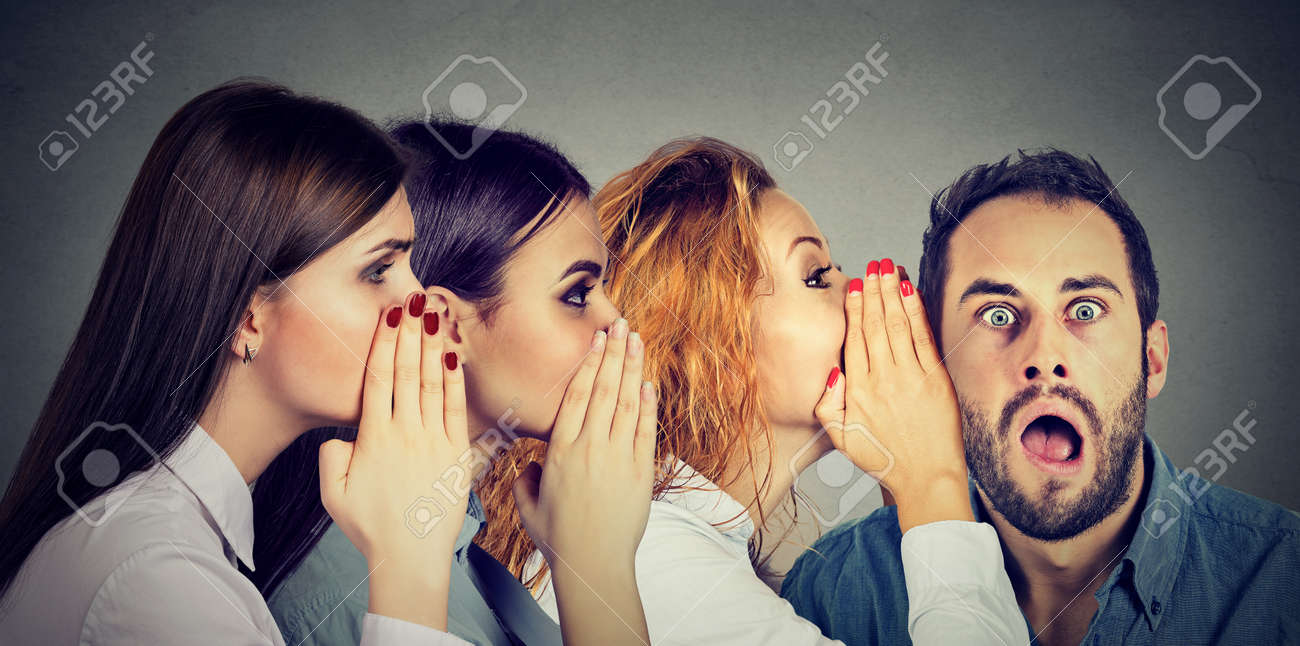 Three young women whispering each other and to the shocked astonished man in the ear. Word of mouth communication concept. Human emotion face expression reaction - 77588224