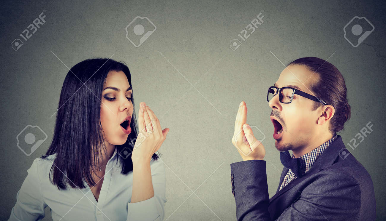 Young couple woman and man checking their breath with hand gesture - 96779698