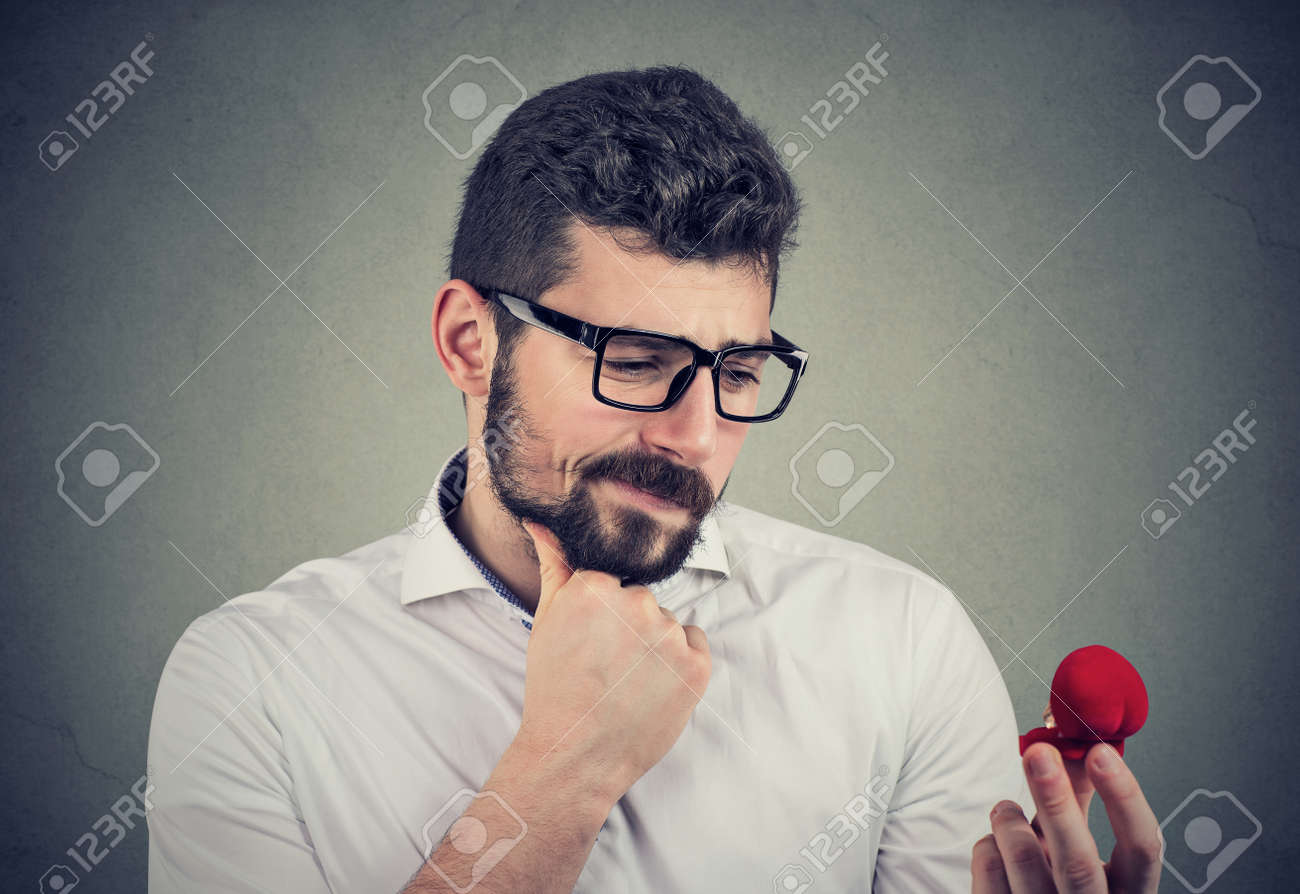 Confused young man looking at an engagement ring and has doubts - 123718908