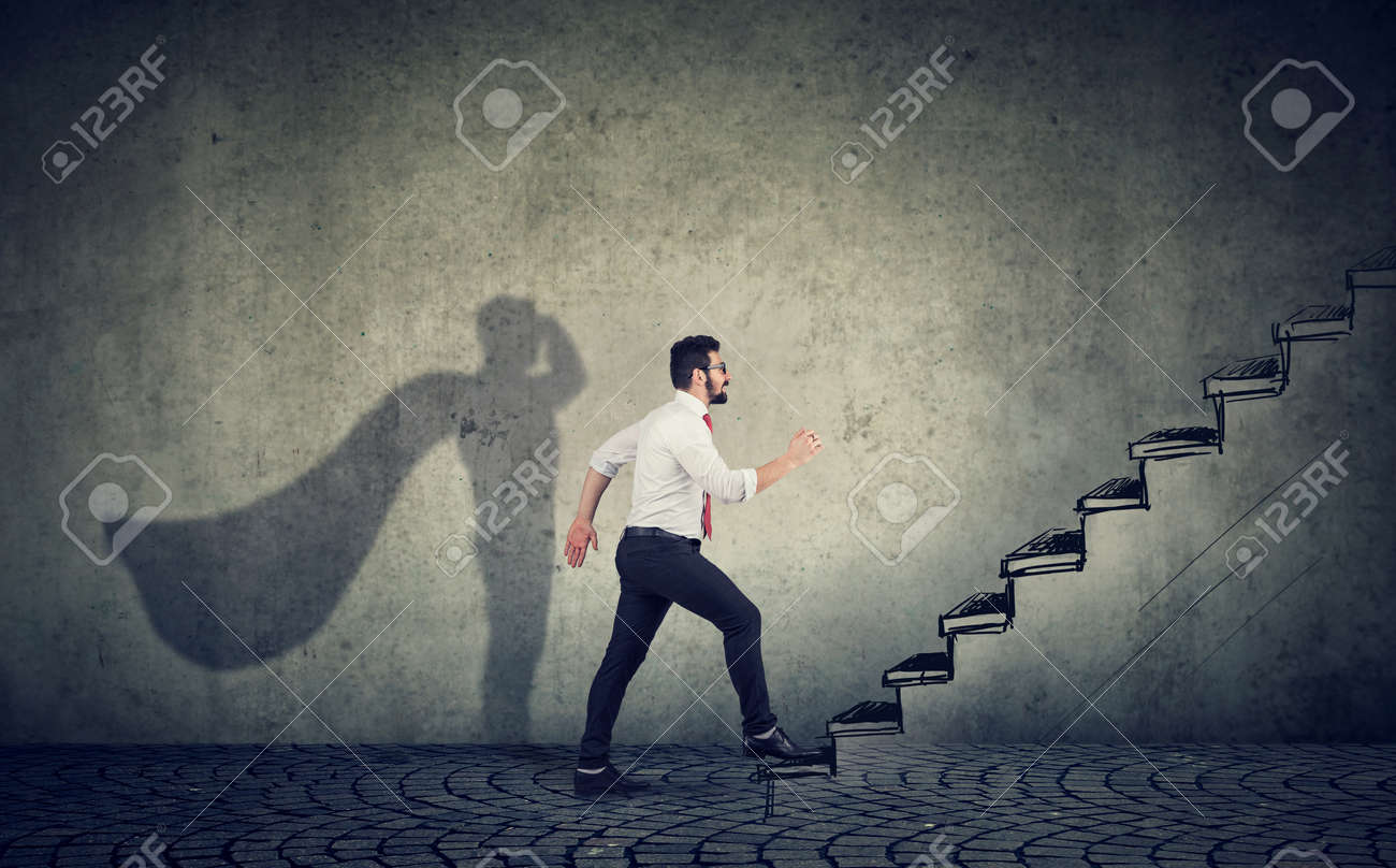 Super hero business man stepping up on stairs climbing to success on gray wall background - 128896939