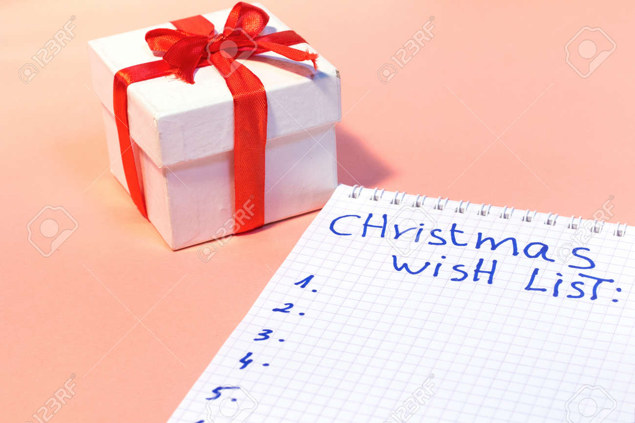 White Gift Box With Red Ribbon And Christmas Wish List Is Writing ...