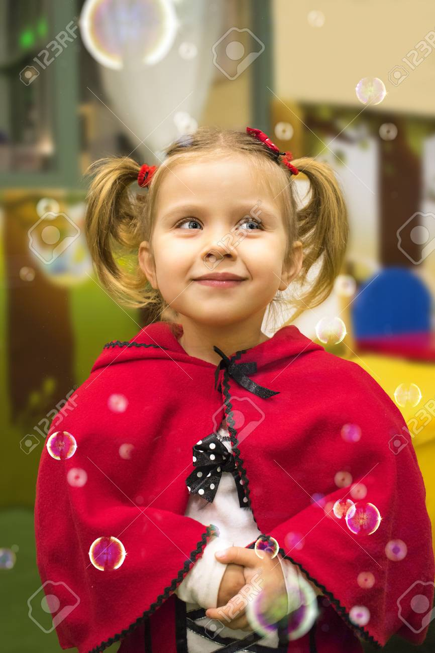 Cute Blonde Little Girl Wearing Red Riding Hood Costume Stock