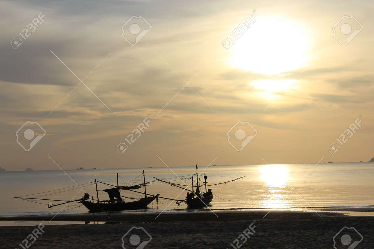 sea and beach landscape with fishing boat and mountain at distance background in early morning sun light Stock Photo - 7447866