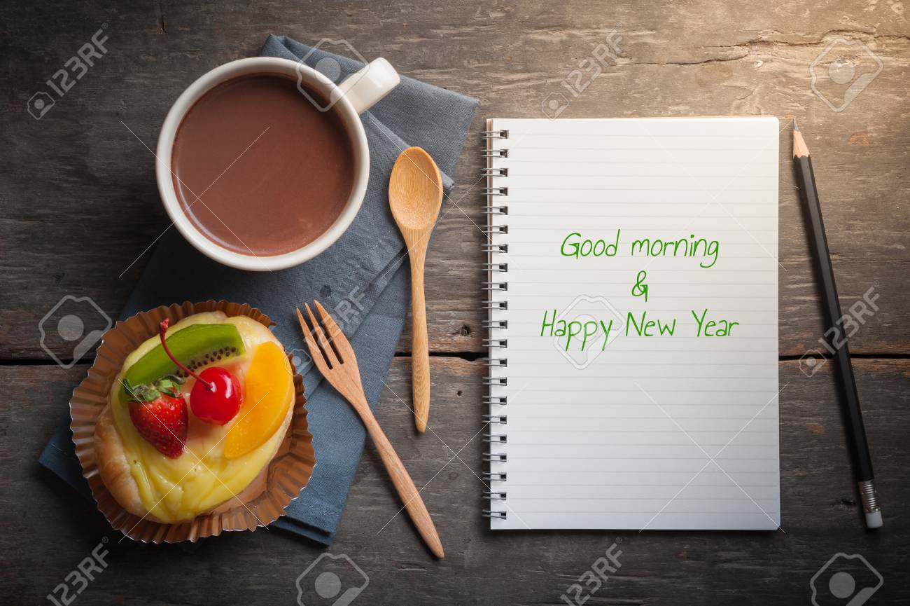 stock photo good morning and happy new year is written on opened notebook with fruit danish pastry and hot chocolate on wood table in morning time