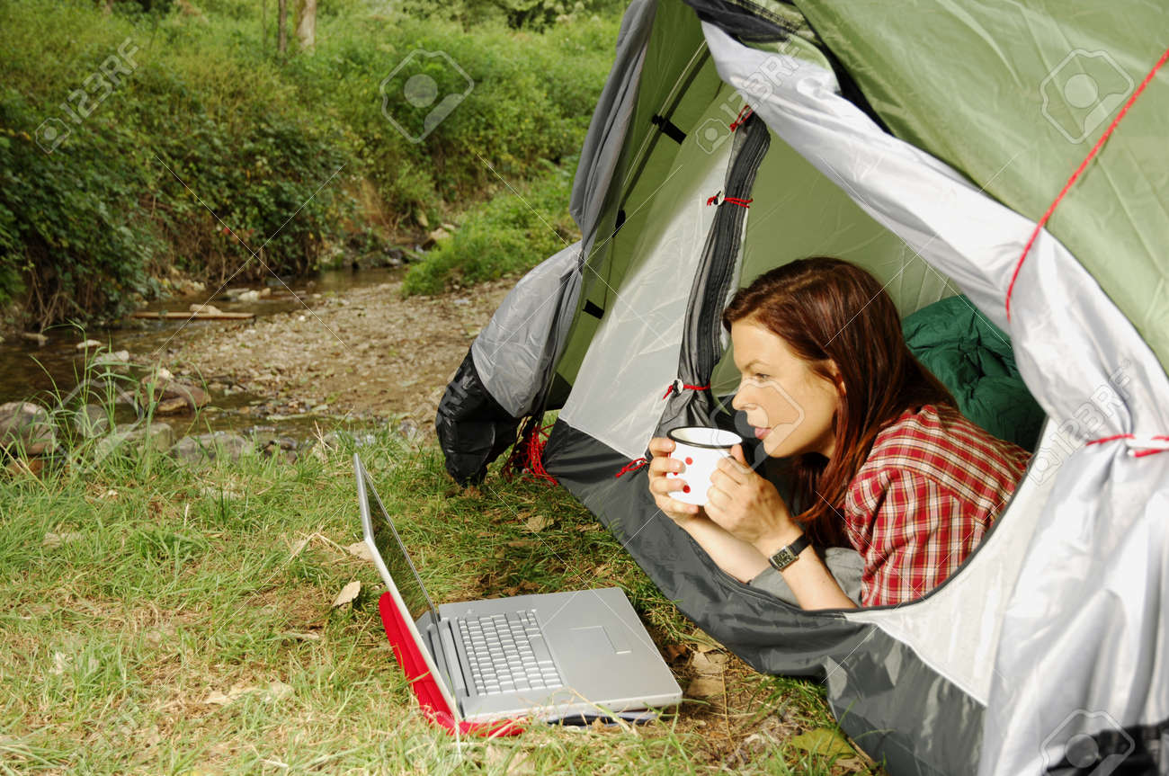 Woman with Laptop lying in a tent Stock Photo - 19631678