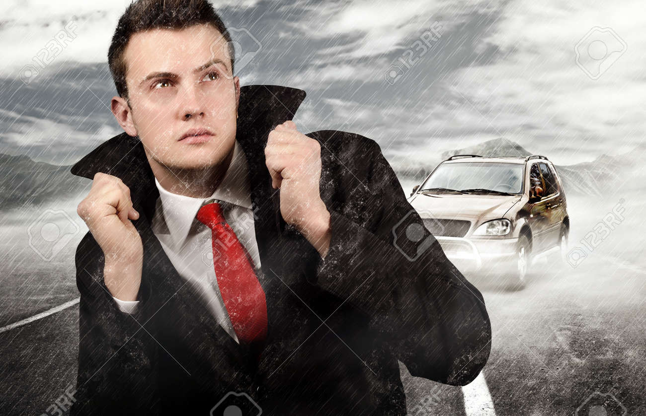 Businessman Walking Trough The Rain After Car Failure Stock Photo ...