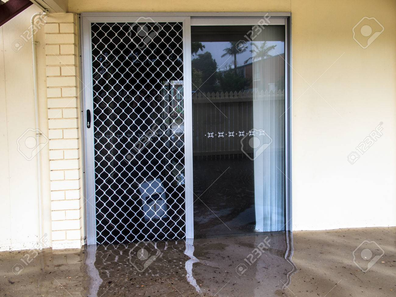 Flood Waters Running Through A Screen Door Stock Photo Picture And