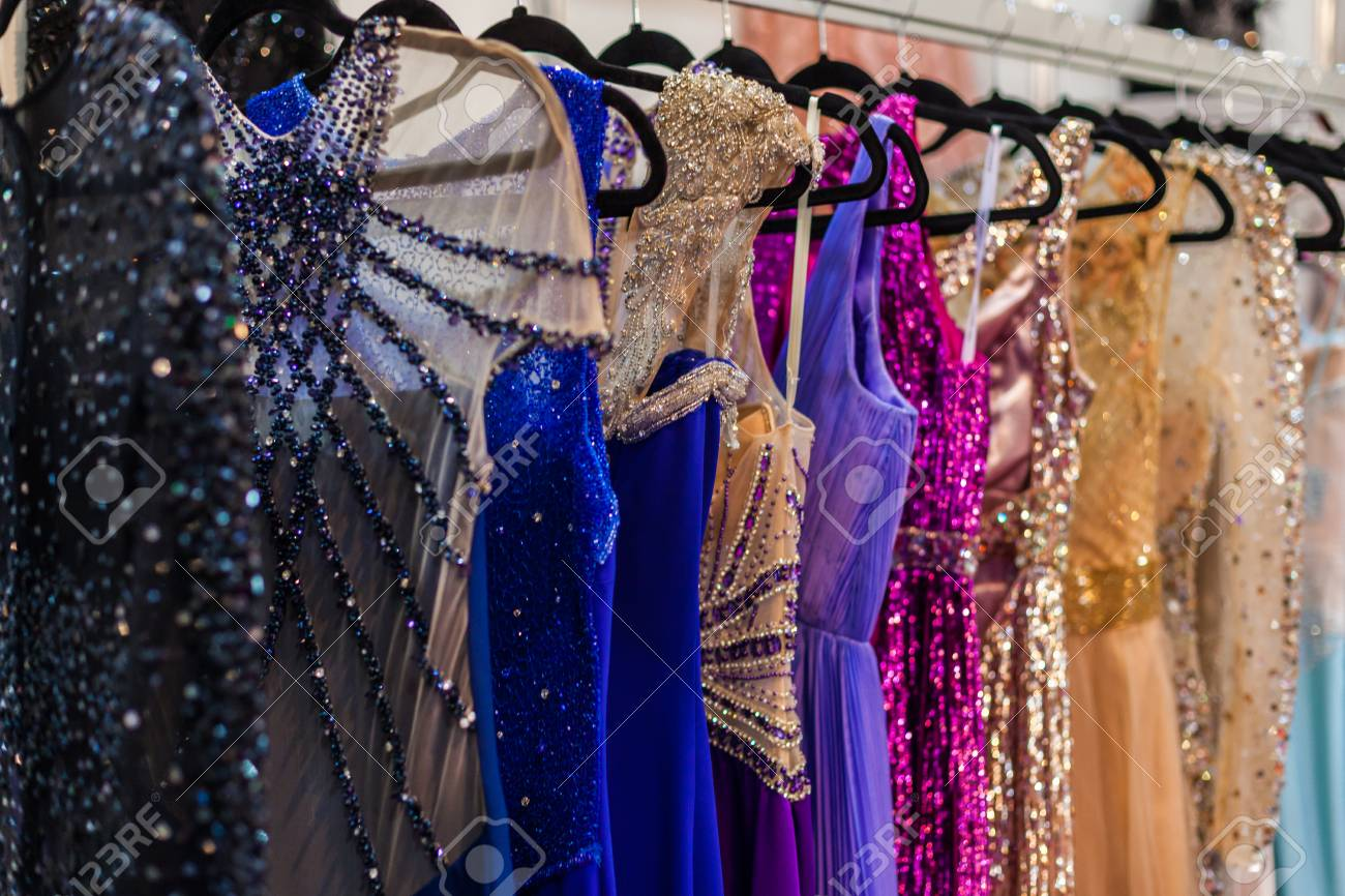 Many brilliant bright evening dresses hanging in a store - 87919249