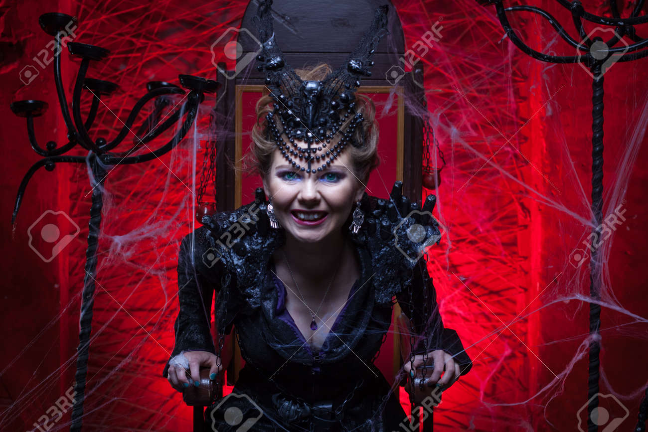 Stock Photo - Woman in a black witch costume sits on a throne in a red room. She growls  sc 1 st  123RF.com & Woman In A Black Witch Costume Sits On A Throne In A Red Room ...