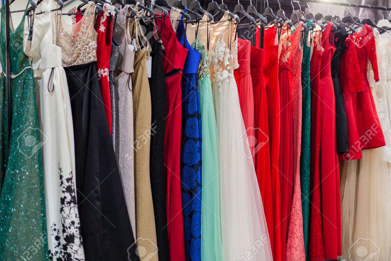 Beautiful elegant evening dresses on hangers in the showroom. - 121838439